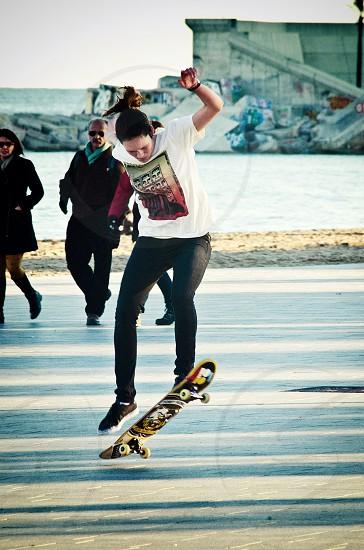 man in white t shirt skateboarding photo
