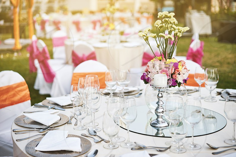 Luxury and beautiful wedding reception dinner table setting with empty glasses of water wine and dinnerware with flower decoration and white fabric cover chairs with pink sash photo