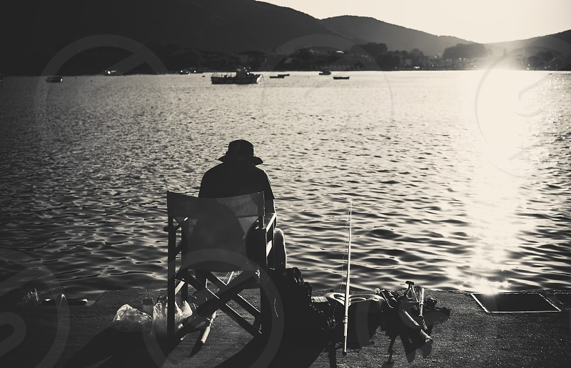 One lonely man sitting and fishing on sea dock during sunset in black and white. photo