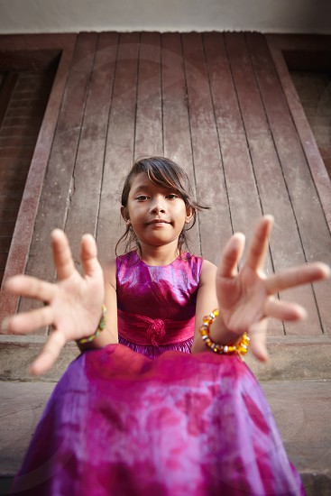 staring; portrait; asian; child; childhood; children; young; 10s; asia; beautiful; cambodia; cambodian; cute; dress; elegant; emotions; expression; female; front view; fun; girl; grabbing; hands; happiness; happy; intense; little; looking; camera; looking at camera; one; outdoors; people; person; pink; posing; pretty; red; sitting; smiling; southeast asia; stare; street; taking; wall; woman; youth photo