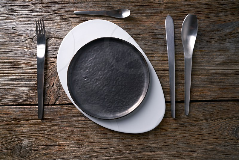 Modern cuisine plate table service with cutlery o aged wooden board photo