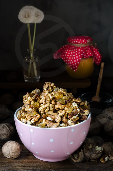 Walnuts in pink bowl with honey on dark background photo