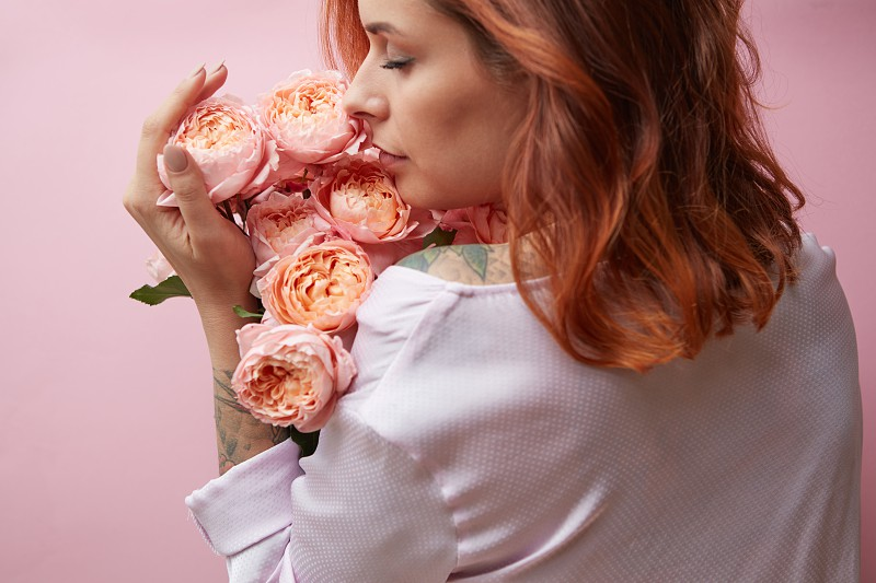 Pink Rose Media. View from the back of a woman sniffing a bouquet of roses. Valentine's Day photo