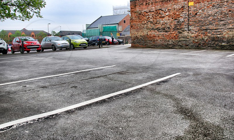 red hatchback parked near grey and white passenger vehicles photo