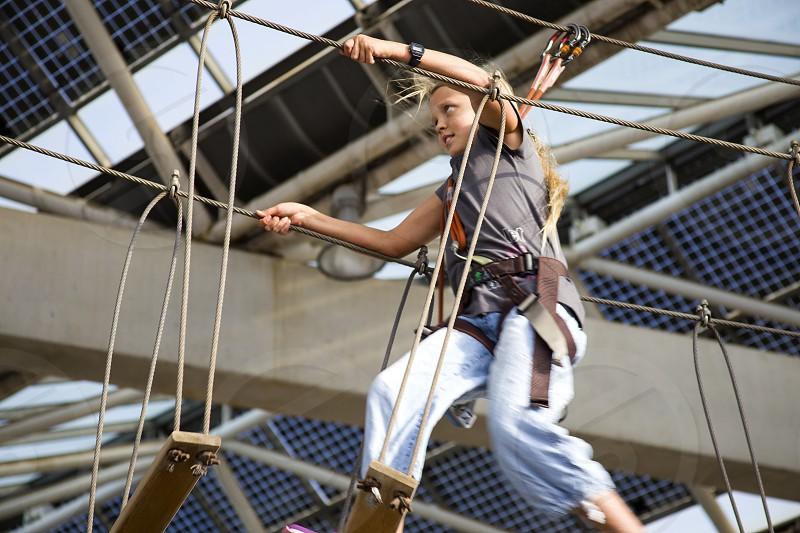 A girl in an adventure park moves over a suspension bridge photo