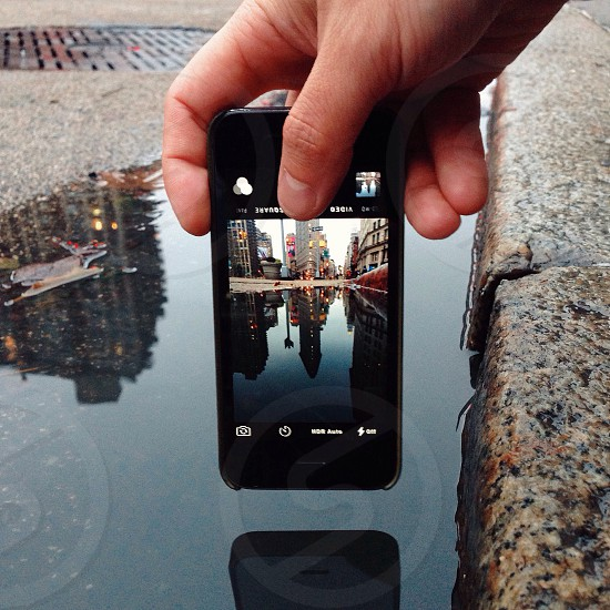 black iphone 4 displaying water surface leading to building photo