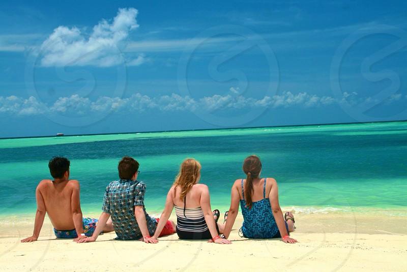 people sitting on beach sand photo