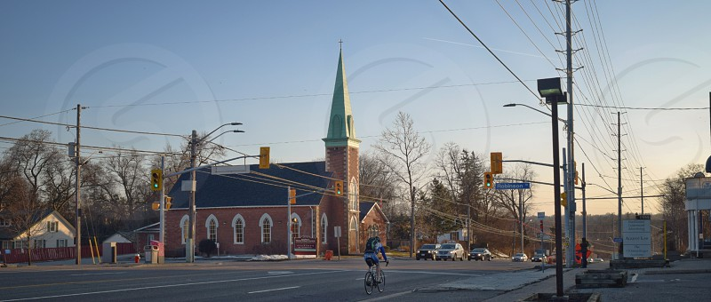 A church along a busy city street with a cyclist pedaling by photo