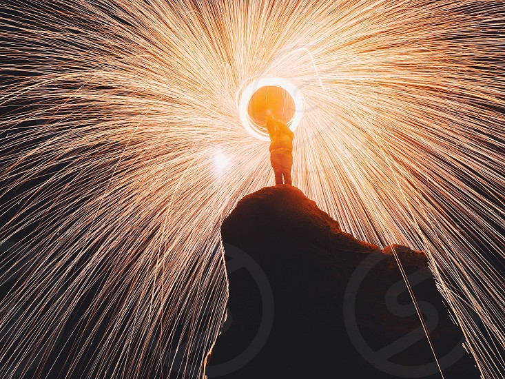 person standing on cliff holding fire cracker at night in time lapse photography photo