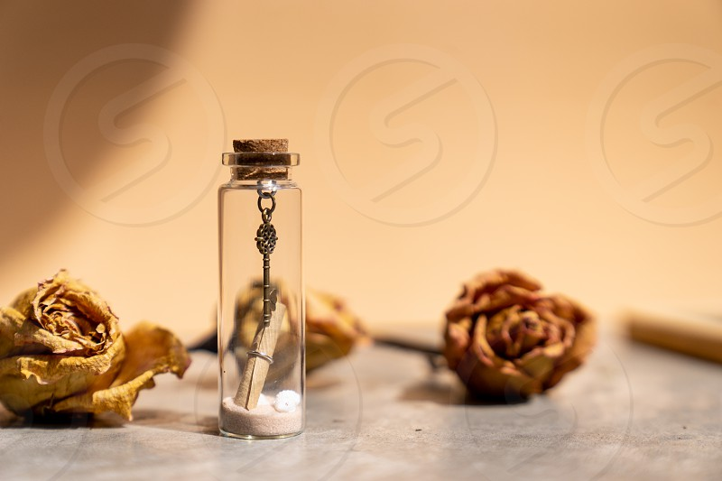 vintage metal key sand and paper letter roll in glass bottle photo