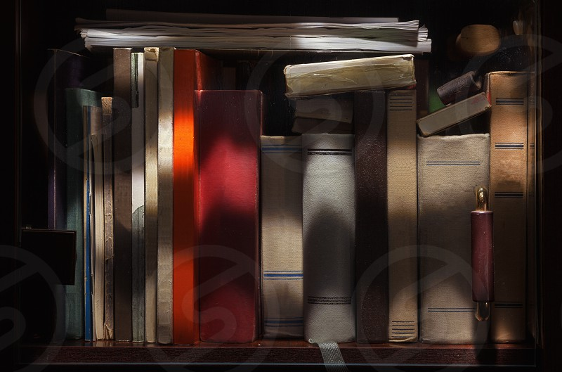 Details of old books in closet details of cover textures under interesting illumination. photo