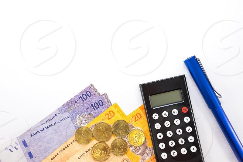 blue pen beside black desk calculator and banknotes photo