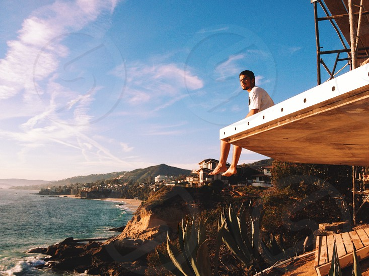 man in white shirt sitting ion wooden ledge photo