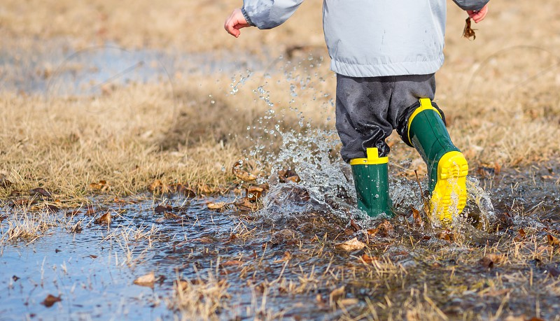 Toddler running in puddles wearing rainboots. photo