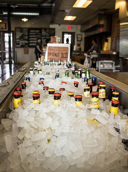 glass bottles covered with white tube ice inside restaurant during daytime photo