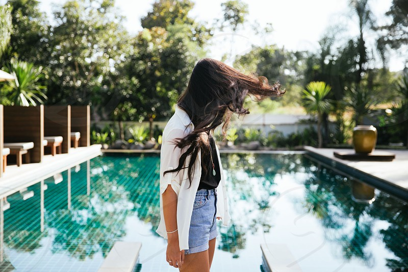 woman in white cardigan near pool photo