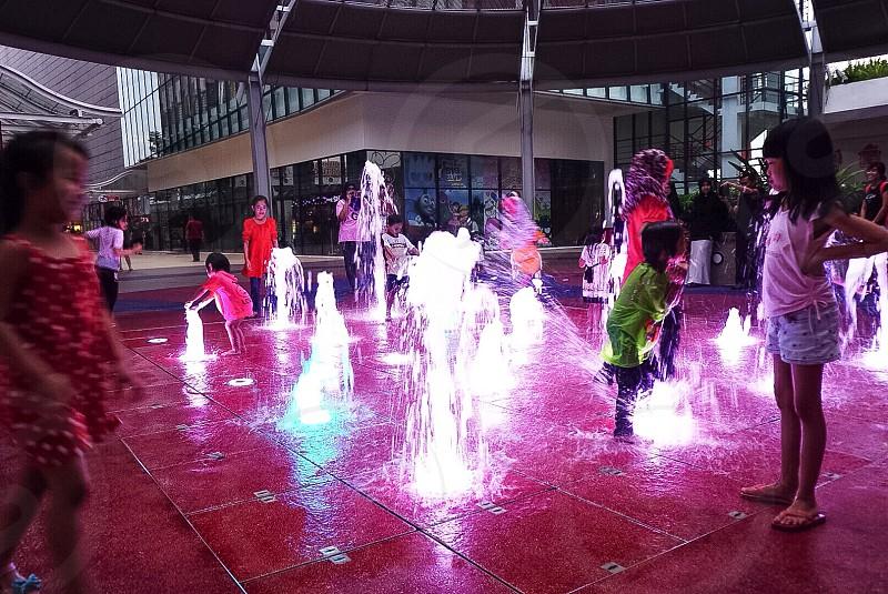 Children having fun playing water fountain photo