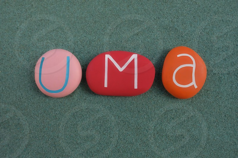 Uma female given name composed with multi colored stone letters over green sand photo