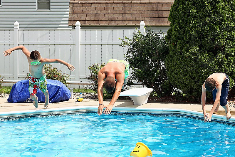three man going to dive on swimming pool during day photo