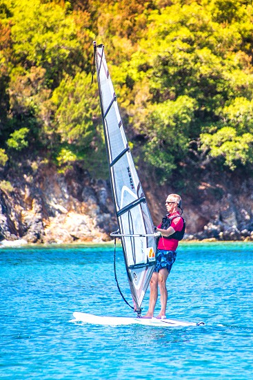 man in red shirt and black swimming vest with blue shorts while doing wind surfing photo