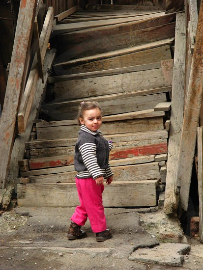 girl in white and black stripe zip jacket and pink pants in front of brown wooden stairs photo