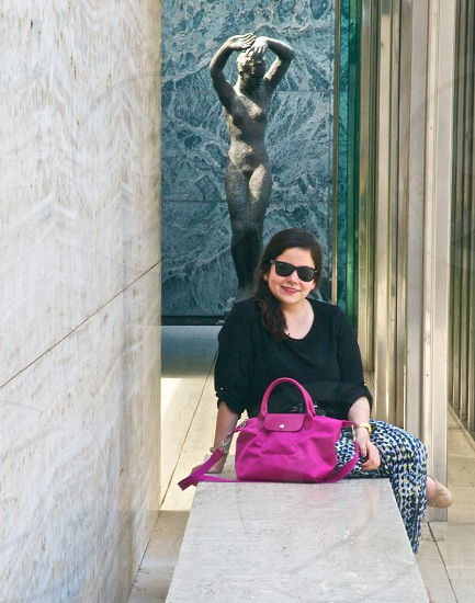 woman in black shirt with pink purse sitting on marble bench photo