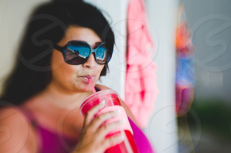 Woman drinking through a straw in summer wearing black sunglasses. Lensbaby effect. photo