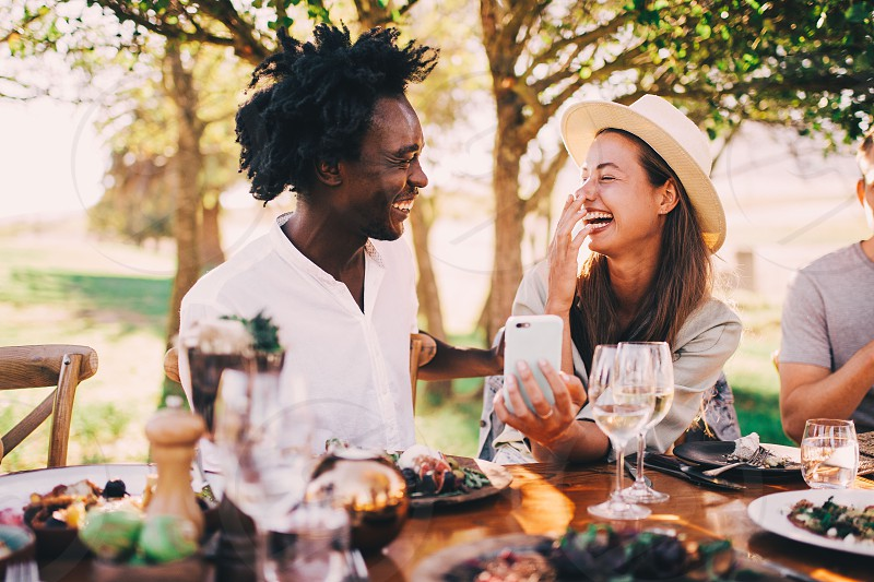 Mixed race couple having fun with phone at dinner party photo