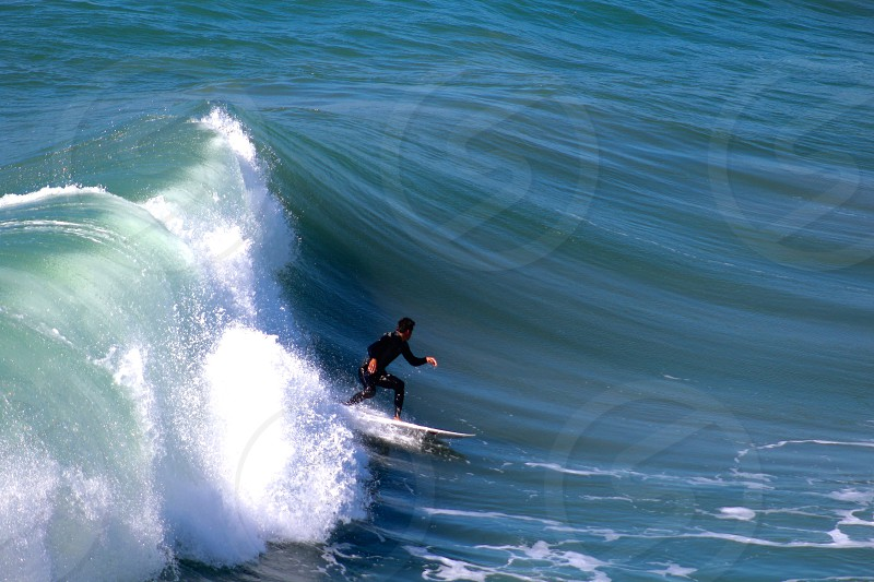 man on black rash guard surfing on giant wave during day time photo