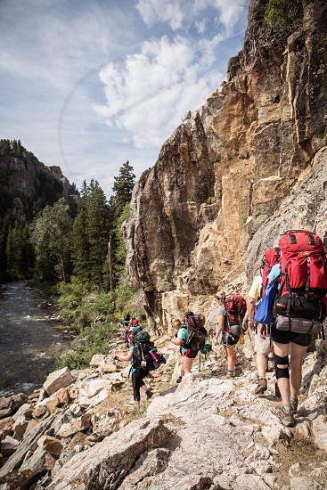 hikers along rocky path near river photo