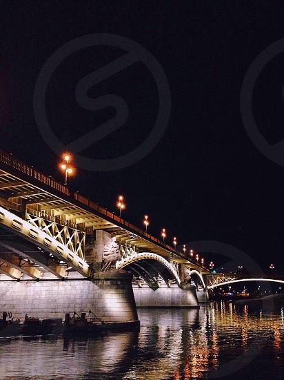 yellow lights beside brown and white metal bridge over body of water during nighttime photo