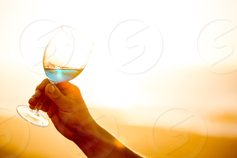 Mens hand holding glass of spanish blue with wine on sea ocean background. photo