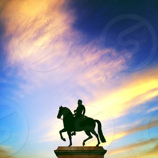 black statue of man riding on horse photo