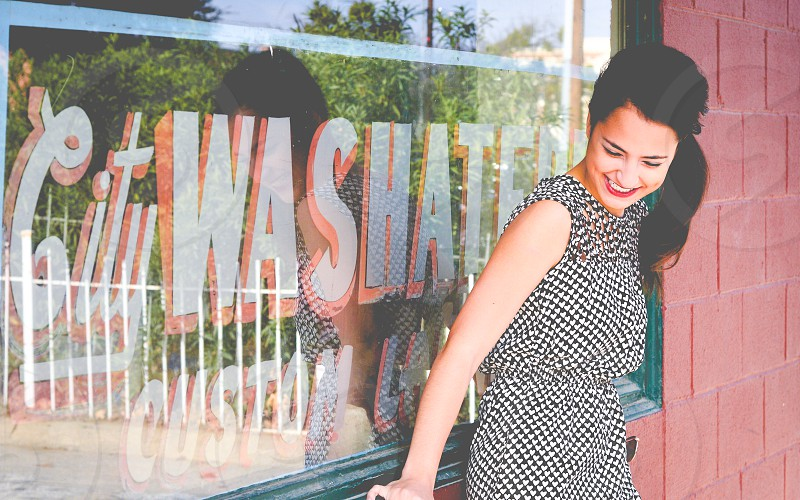 Laughing smiling girl next to window front sign for laundromat.  photo
