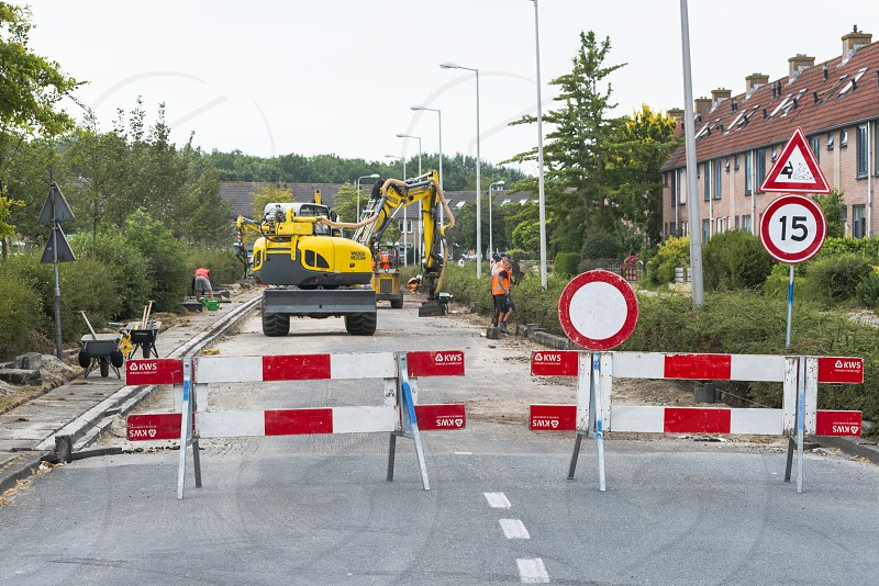 HellevoetlsuisNetherlands-12-July-2018:construction workers are busy in renewing the road in the villageone in a white the streets have to get new asphalt and will be blocked photo