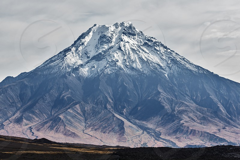 Beautiful autumn volcanic landscape - view of snow-capped cone of stratovolcano Bolshaya Udina Volcano in Klyuchevskaya Group of Volcanoes. Russian Far East Kamchatka Peninsula Eurasia. photo