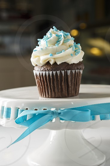 Single chocolate cupcake with vanilla frosting and teal colored sprinkles on a cake stand photo