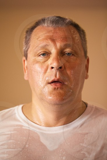 Tired looking hot perspiring middle-aged man after a workout closeup head and shoulders portrait looking directly at the camera photo