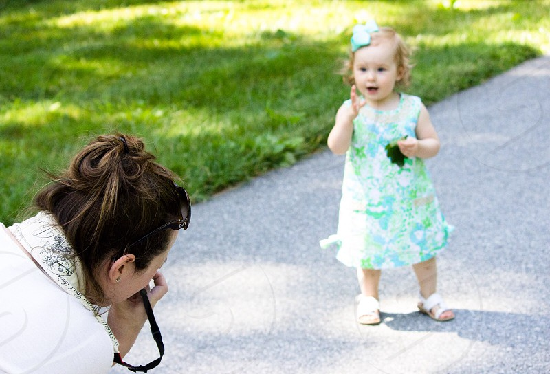 woman taking a photo of a girl wearing a teal and white floral sleeveless dress photo