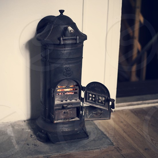 In front of the fire place an old and beautiful vintage wood burner at work photo