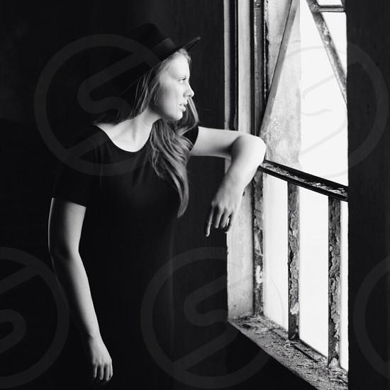 woman in black scoop neck dress wearing hat leaning on window photo