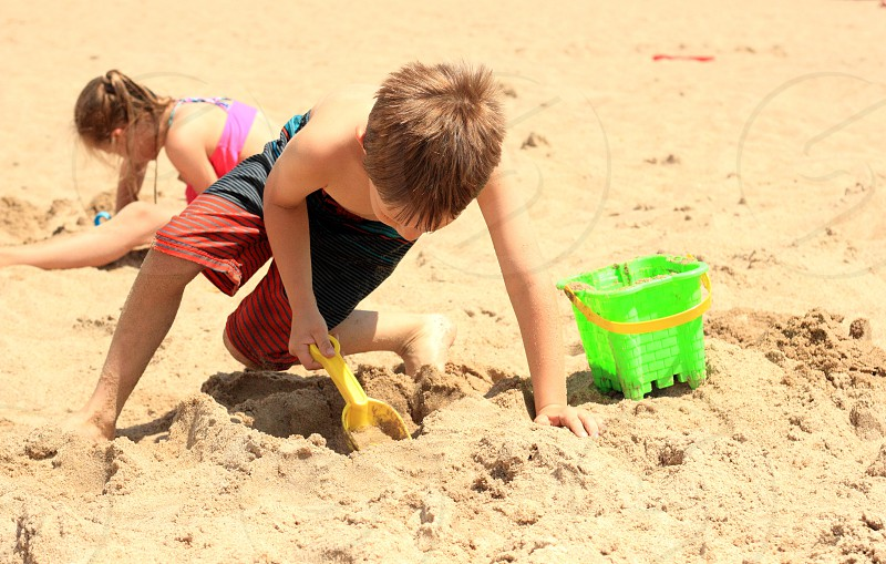 Boy girl sand sandy kid child beach summer vacation son daughter green Paul bucket people children scoop play playing leisure  photo