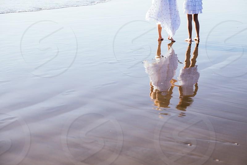 2 ladies walking on seawater  photo