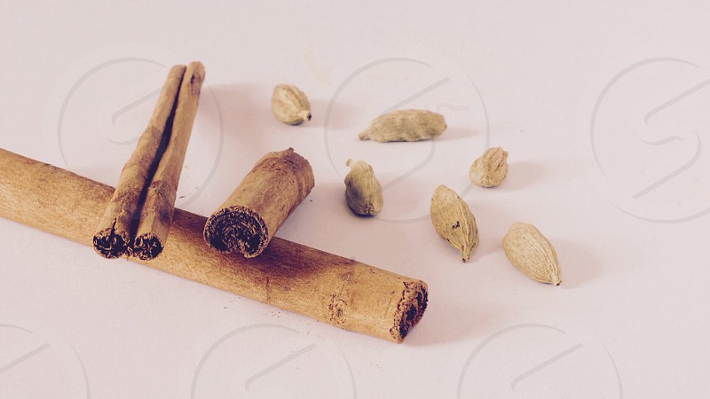 3 sticks of cinnamon and nuts on white table photo