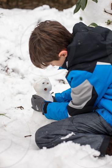Building snowman outside photo