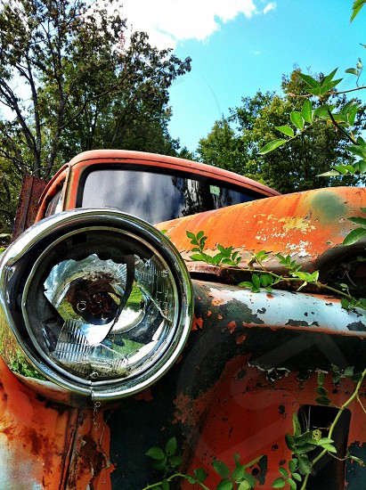 orange classic car with broken head light photo