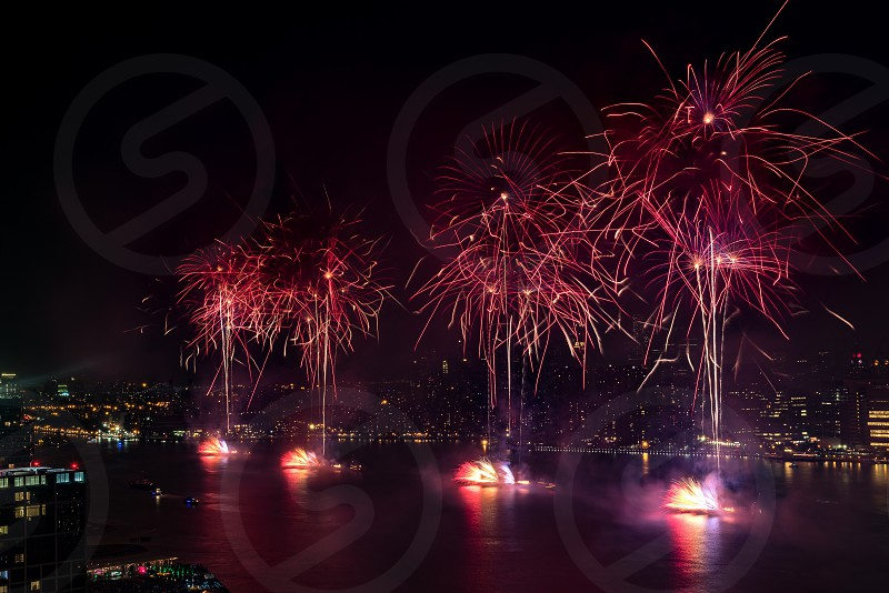 aerial fireworks display above body of water near city photo