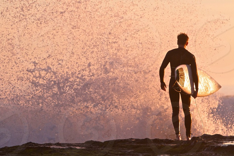 man with surfboard on the beach photo