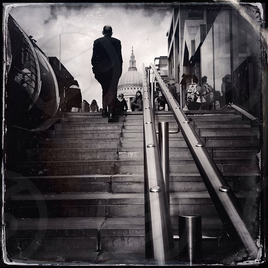 man wearing black suit walking up staircase photo