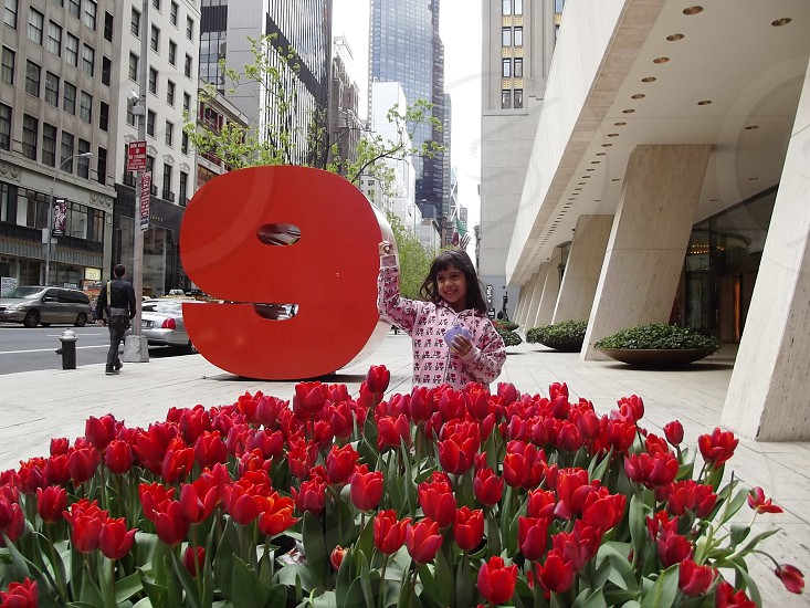 girl stainding in front of red tulips photo